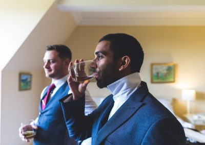 Groom having a drink of whiskey before he gets married with his bestman