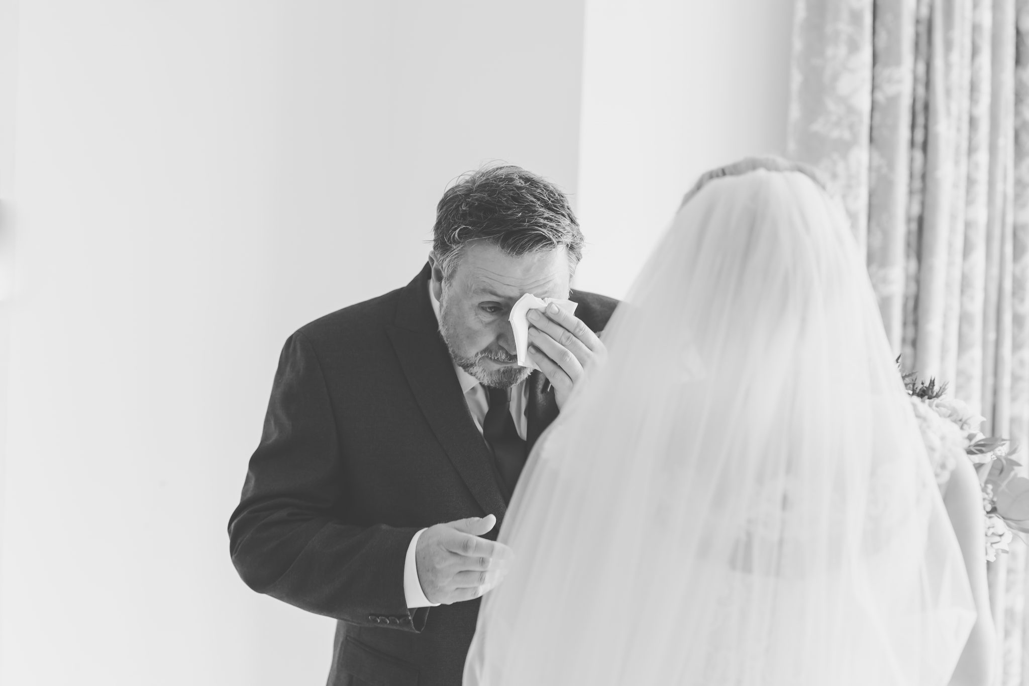 father of the bride has an emotional moment after seeing his daughter in her wedding dress