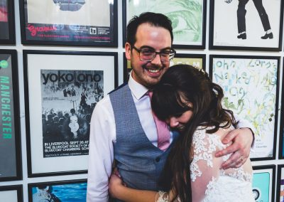 Bride & Groom hugging next to posters at Bluecoat Liverpool