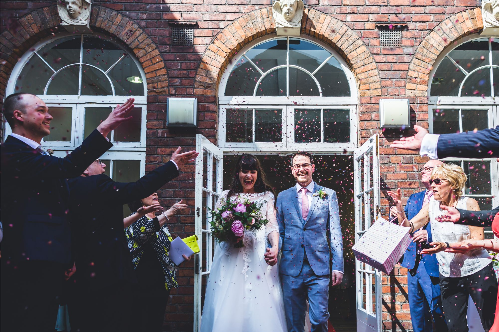Bride and Groom showered with confetti after wedding ceremony in the Sandon Room at Bluecoat Liverpool