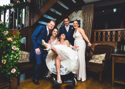 Bride and Groom with guests having a laugh in Nan's wheelchair