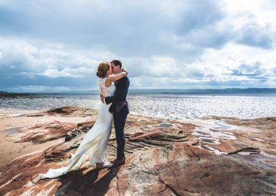 Bride and Groom holding each other on top of rocks on the beach