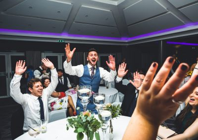 Wedding guests doing a Mexican wave at their table in the evening
