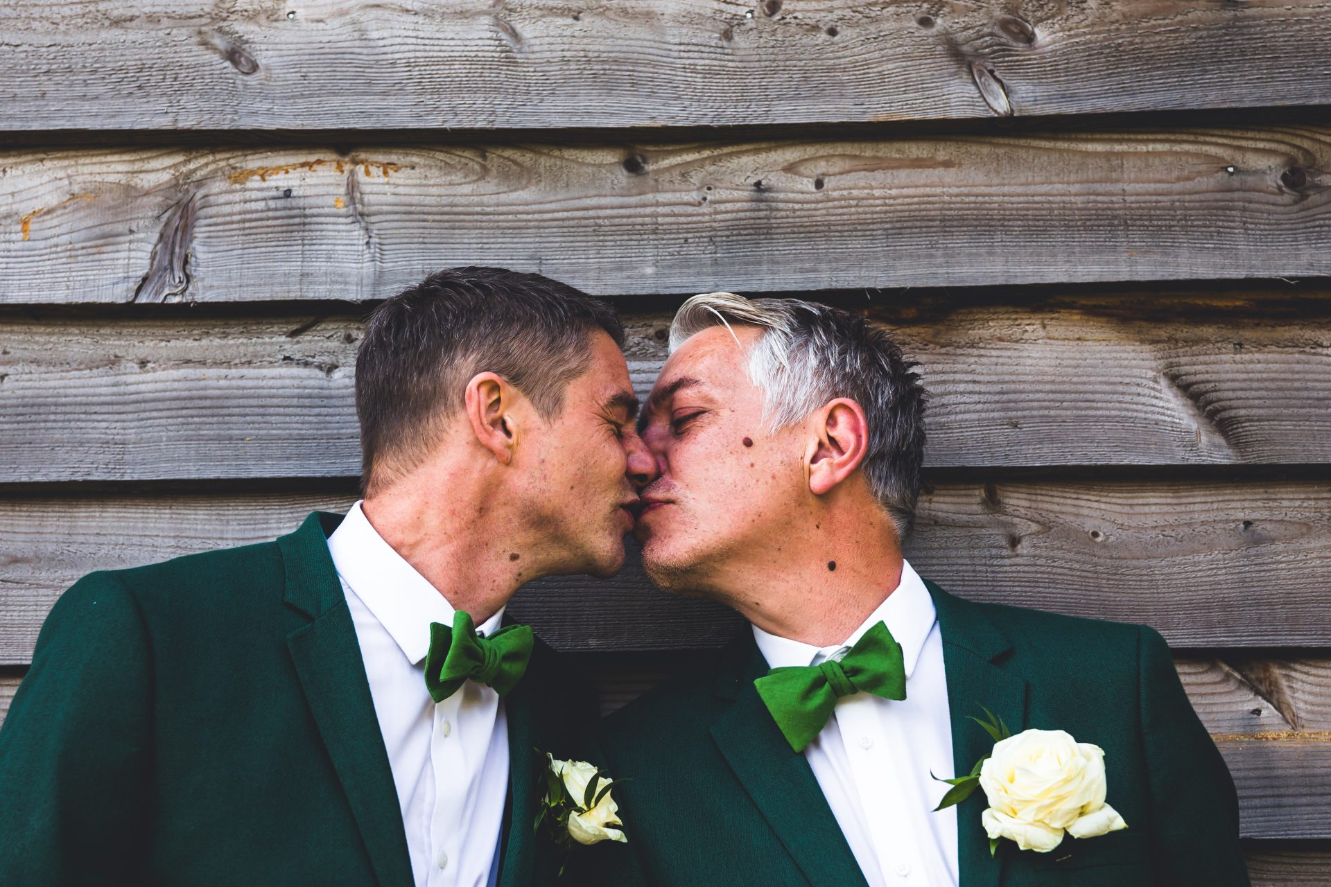 Groom and Groom husband and husband having a kiss in their green suits at their wedding