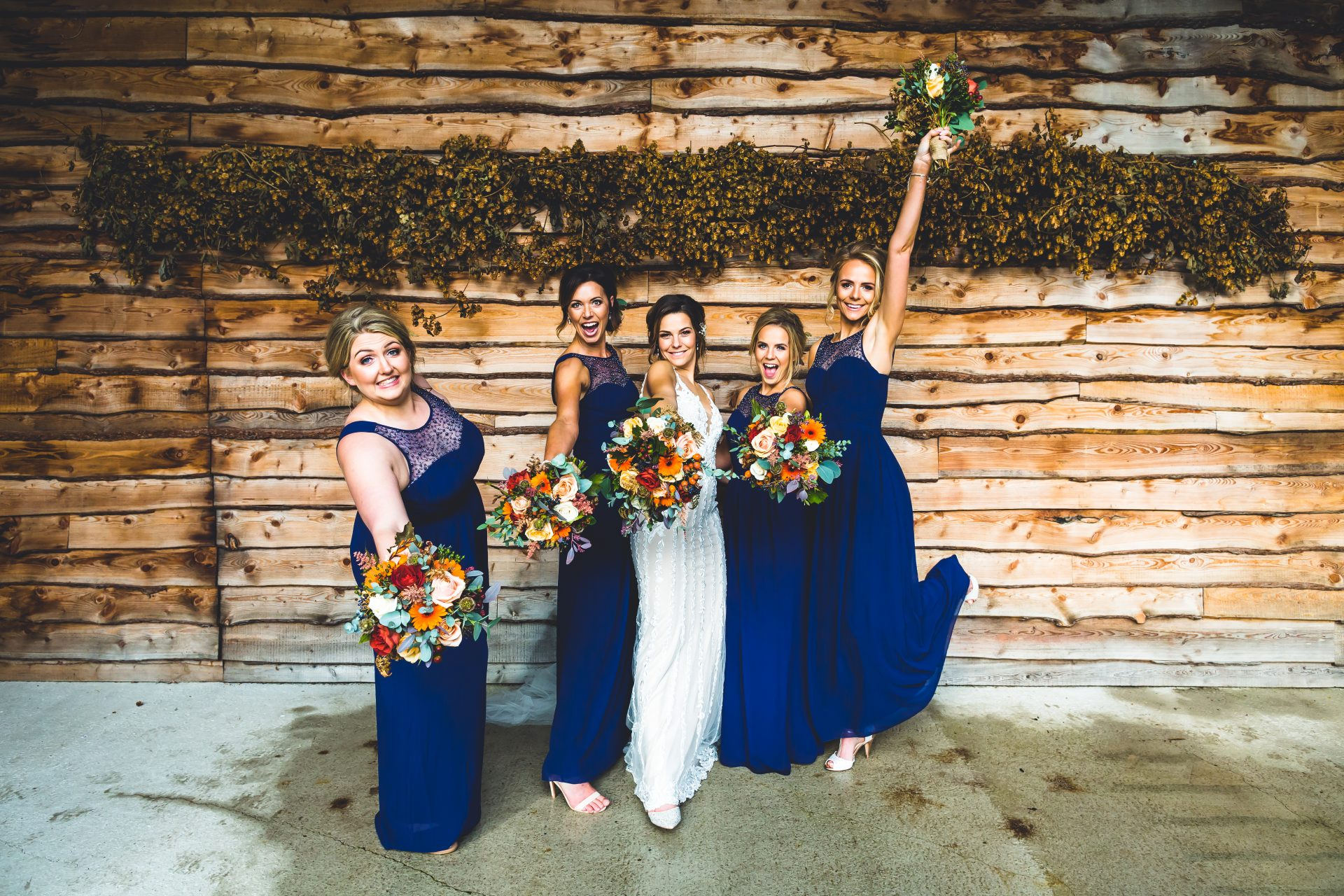 Bridesmaids and Bride free styling the group shot with wedding flowers in the air