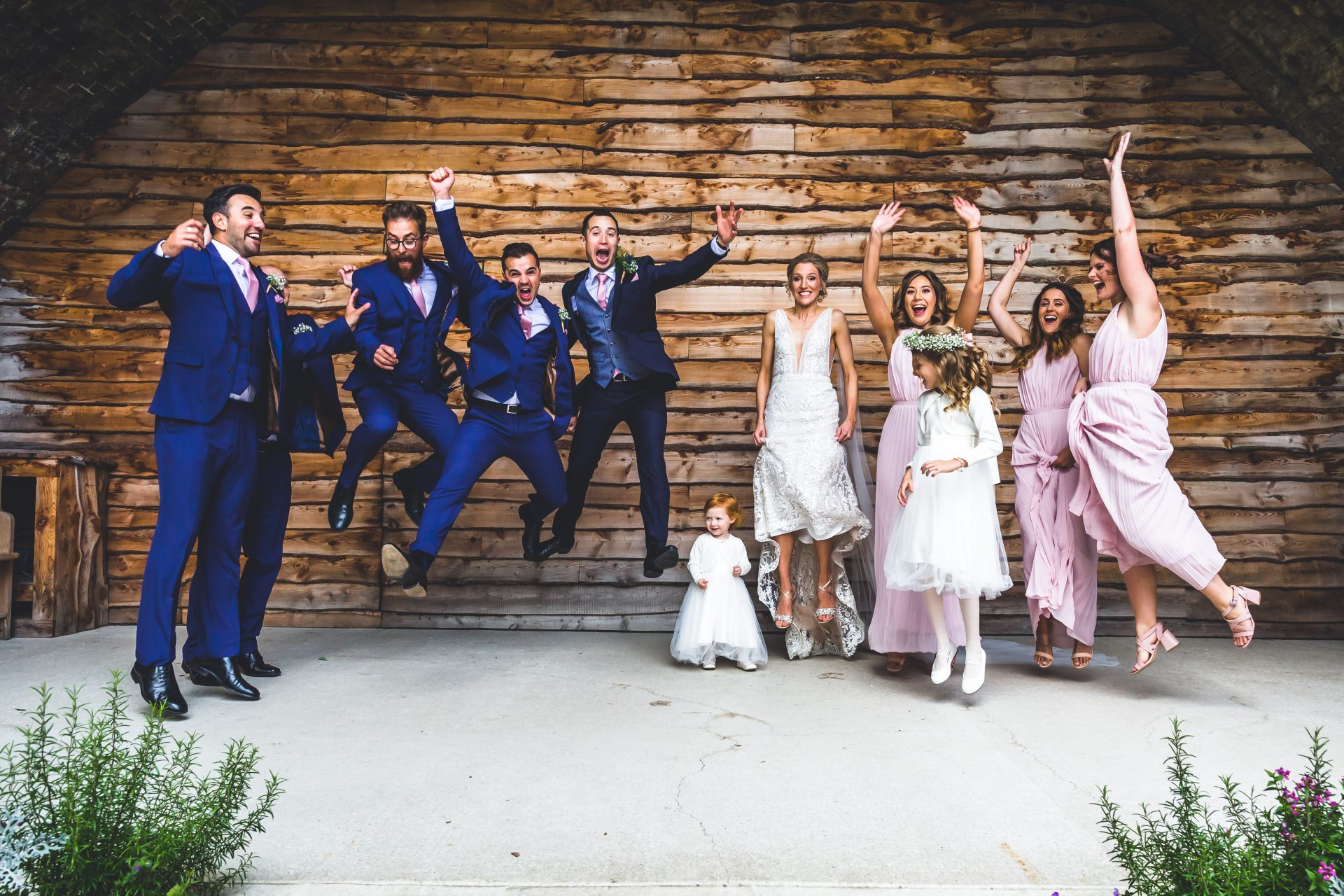 Group shot of bride and groom with grooms men and bridesmaids jumping in the air