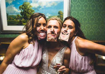 Bride and bridesmaids with funny mouth cards on face at the wedding