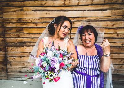Bride with a guest giving her a funny look with brides veil on her head