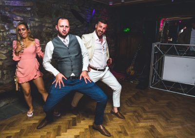 Wedding guests doing lunges on the dance floor in the evening